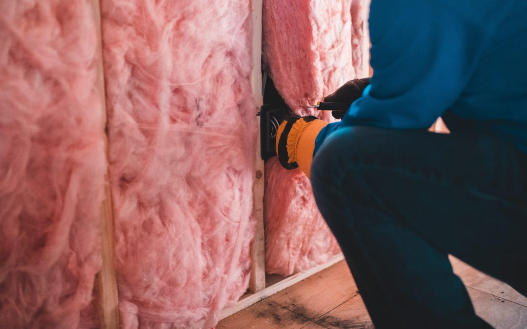 Home repair technician installing insulation